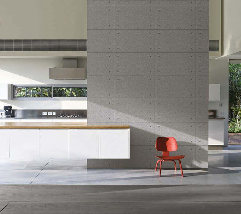 Red moulded chair against concrete wall in house designed by Weinstein Vaadia Architects, Hofit, Israel., Architects: Architects: Weinstein Vaadia Architects