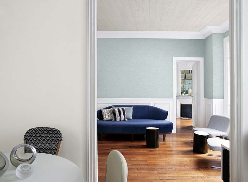 Open plan living and dining area in with table, sofa and mirror in French apartment.